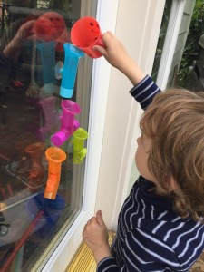 Child pouring water into Boon Building bath pipes stuck on glass door