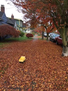 Tonka yellow dump truck on sidewalk covered in fallen leaves autumn fall