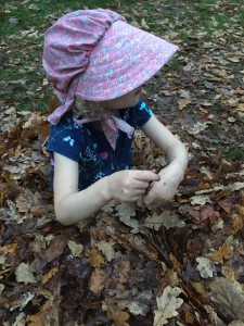 Young girl in pink bonnet sitting in pile of leaves