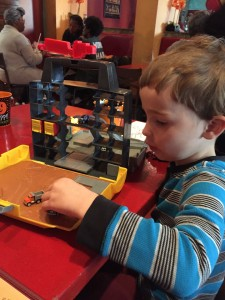 Child playing with Tonka Tinys Cityscape Carrying Case Playset at restaurant table
