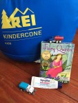 REI Kids Kindercone sleeping bag, Fairy Queen card game, Aquaphor tiny tube, Driven pocket series tiny truck