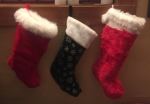 Three Christmas stockings hung from window