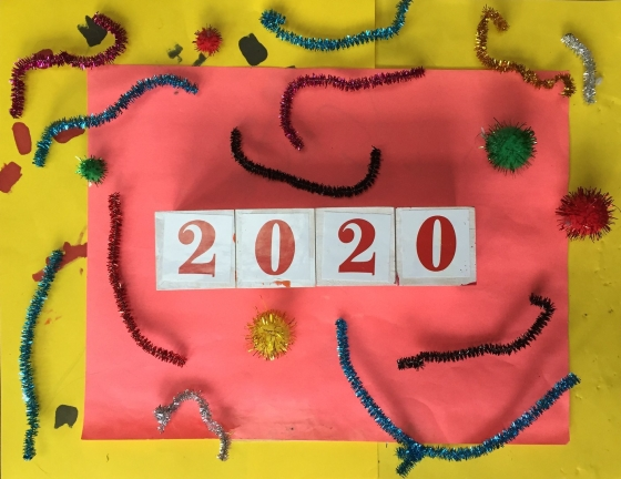 2020 year in blocks on orange and yellow background with sparkly pipe cleaners and puff balls