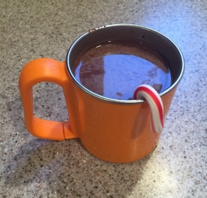 Kids orange mug with hot cocoa and miniature candy cane stirrer