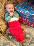 Infant wearing green and white striped pajamas in red Christmas stocking on sofa next to stack of presents