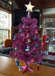 Pink miniature artificial Christmas tree with white star on top and tiny decorations