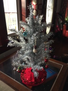 Silver tinsel miniature artificial Christmas tree with tiny red tree skirt and few decorations