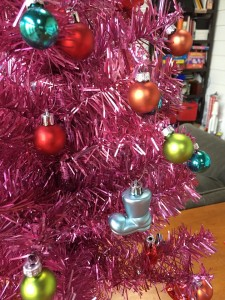 Tiny Christmas ornaments on miniature pink artificial fake Christmas tree