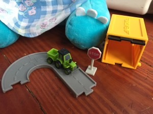 Driven Pocket Series vehicles with opening garage in yellow and black, green tractor with trailer, three connecting gray road pieces, and tiny stop sign