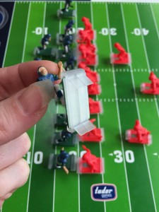 Plastic cleats on the bottom of NFL team figure from electric football game