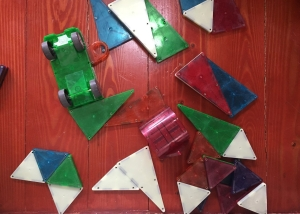 Magna-Tiles scattered on hardwood floor including magnet car and glow in the dark tiles