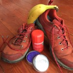 Tennis shoes sneakers running shoes Columbia with banana, LUSH solid shampoo in open tin, and Myro Solar Flare deodorant