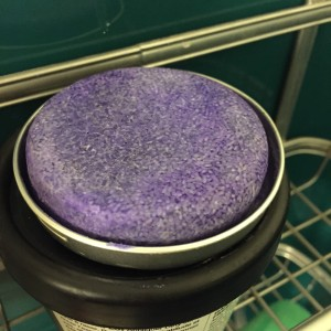 LUSH solid shampoo in reusable tin inside shower caddy
