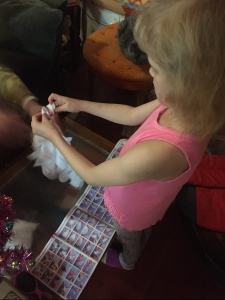 Young girl tying knots to create unicorn hoodie blanket with Make It Real Kit