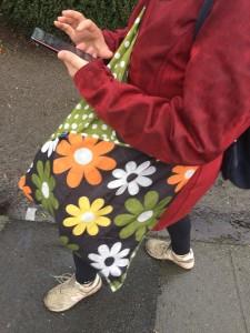 Envirosax Slingsax Messenger Bag in green orange brown daisy print carried across body of woman using phone