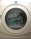 Front load gas Maytag dryer filled with laundry sheets towels