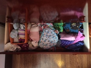 Laundry clothes put away in bottom drawer of child's dresser socks in bin underwear pajamas swim suits
