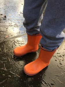 Child wearing bright orange with blue trim Norty rubber rain boots for kids