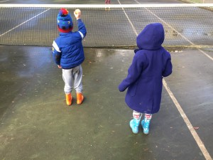 Two kids wearing Norty rain boots in orange and blue unicorn and rainbow print