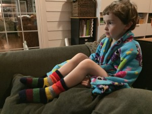Kid sitting on top of sofa cushions in pile