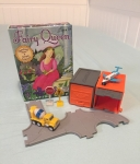 Driven tiny cars garages and road signs next to Fairy Queen card game in box on twin mattress