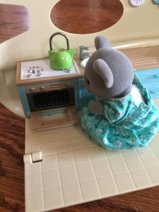 Calico Critter mouse in turquoise dress in Caravan Family Camper kitchen open oven with green teapot on top