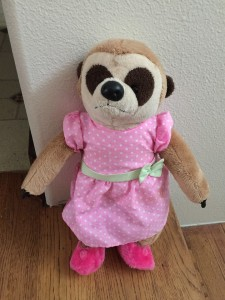 Meerkat stuffed animal in pink polka dot dress with pink fuzzy slippers
