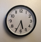 Round clock with numbers analog at 5:34 on white wall