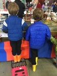 Child in blue jacket standing on Acko folding step stool at train show watching trains