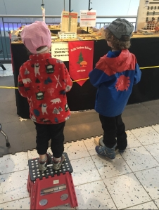 Child in red Hatley fleece jacket standing on red Acko folding step stool watching model trains on display