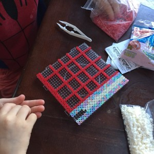 Perle beads on clear pegboard with kids' hands holding beads
