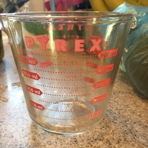 Glass pyrex measuring cup on kitchen cabinet