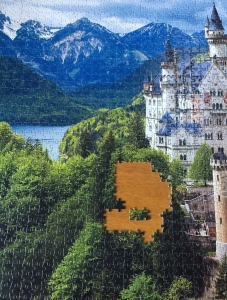 Neuschwannstein castle 2000 piece puzzle mostly completed with hole and puzzle piece in center of green trees snowy mountains and water in backdrop