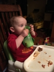 Toddler in high chair seat drinking from green sippy cup with lid