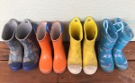 Croc Bump It and Norty kids rain boots four pairs in a row on a wooden porch floor shark print, orange and blue, bright yellow, and blue unicorn print