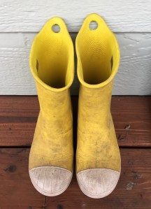 Crocs Bump It Rain Boots in bright yellow with white toe and soleon wooden porch