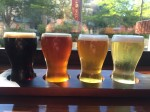 Beer flight from dark to light in front of window with sun shining through four glasses