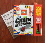 Driven tiny dump truck on top of Lego Chain Reactions book on top of The Pigeon Needs a Bath by Mo Willems