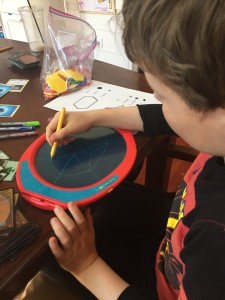 Nine year old boy drawing on boogie board at table