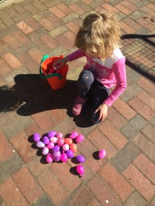 Girl with pink and purple plastic Easter eggs sorted by color to hunt