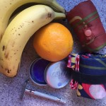 Bananas, oranges, LUSH purple solid shampoo, reusable razor, envirosax reusable bags on counter