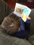Nine year old boy reading book on sofa