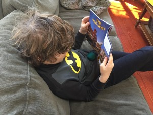 Nine year old reading about the Wild West while sitting on green sofa