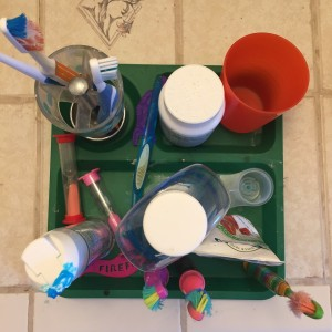 Kids' toothbrushes, mouthwash, timers, cup, and vitamins corralled on toddler divided section plate as seen from above