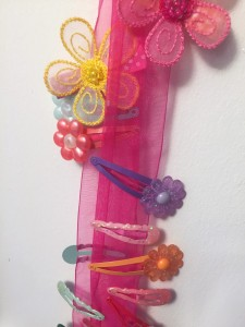 Child's colorful barrette hair clips hung on sheer pink ribbon
