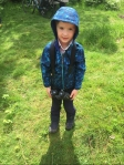 Five year old in blue camouflage rain jacket with binoculars hanging around neck standing on grass