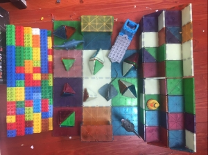 Magna-Tiles stadium with stands built by nine year old with Duplo crowd stadium seating on opposite side