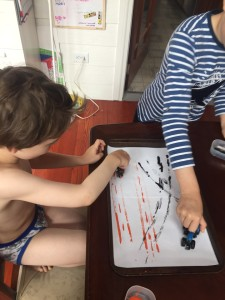 Two boys painting on paper with cars