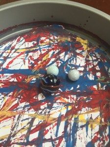 Marbles in cake tin with paper on bottom painted by rolling balls around