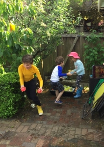 Kids playing with water balloons in yard